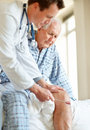 Doctor checking old man knee using a reflex hammer Royalty Free Stock Image