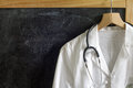 Doctor coat with stethoscope on blackboard