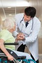 Doctor comforting senior patient at hospital happy young male Royalty Free Stock Image