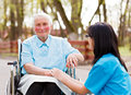 Doctor consoling elderly lady beautiful nurse in blue coat walking a kind in wheelchair in park Stock Photo