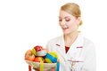 Doctor dietitian recommending healthy food diet woman in lab coat holding fruits and measure tapes isolated with Royalty Free Stock Photos