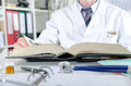 Doctor doing research in a medical book Royalty Free Stock Photo