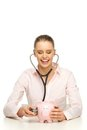 Doctor examining piggy bank with stethoscope Royalty Free Stock Photos