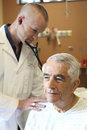 Doctor examining senior man with stethoscope male men in clinic Royalty Free Stock Photo