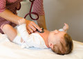 Doctor exams infant with stethoscope Royalty Free Stock Photo