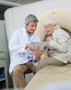 Doctor explaining female patient mature male with a book to senior Royalty Free Stock Photo