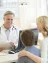 Doctor explaining report to mother and son in hospital happy mature male at desk Royalty Free Stock Photo