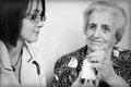 Doctor giving medicin medicines and explaining how to take pills to elderly women at home Royalty Free Stock Image