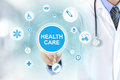 Doctor hand touching HEALTH CARE sign on virtual screen Royalty Free Stock Photo