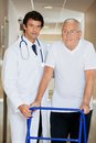 Doctor helping an old man with his walker young handsome men Royalty Free Stock Images
