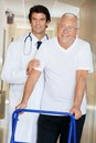Doctor helping an old man with his walker young happy men Royalty Free Stock Image