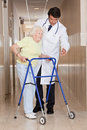 Doctor helping patient use walker a assisting a senior women onto her Royalty Free Stock Images