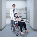 Doctor helps young mother and her baby portrait of pushing a wheelchair with a Stock Images