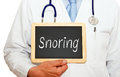 Doctor holding board marked snoring with stethoscope in white clinical coat a chalk with the text written on it Stock Photo