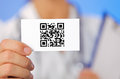 Doctor holding business card with QR code