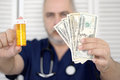 Doctor holding cash and pills Royalty Free Stock Image