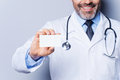 Doctor holding copy space close up of confident mature showing his business card and smiling while standing against grey Royalty Free Stock Photography