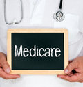 Doctor holding medicare sign physician or medical person a small chalkboard with the word Royalty Free Stock Images