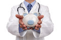 Doctor holding piggy bank Stock Image