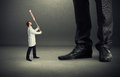 Doctor holding placard small screaming and looking up at big legs over dark grey background Royalty Free Stock Images
