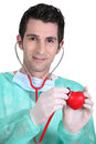 Doctor holding plastic heart Royalty Free Stock Photo
