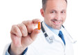 Doctor holding and showing one transparent pill of fish oil Royalty Free Stock Photo