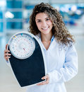 Doctor holding a weight scale happy at the hospital Stock Photography