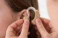 Doctor inserting hearing aid in the ear of a girl close up Stock Image