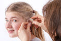 Doctor inserting a hearing aid into young girl s ear in front of white background Stock Photo