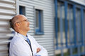 Doctor leaning on wall while looking away thoughtful mature Stock Photos