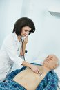 Doctor listening heartbeat of patient by phonendoscope in clinic hospital Royalty Free Stock Photography