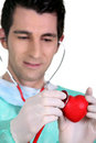 Doctor listening to the heartbeat of a heart Stock Image