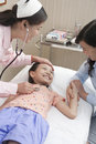 Doctor listens to little girl s heartbeat girl is smiling Stock Photos