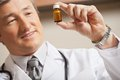 Doctor looking at medicine bottle mature male smiling while Stock Image