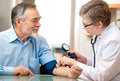 Doctor measuring blood pressure male patient Royalty Free Stock Photo