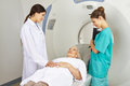 Doctor and mta talking with patient on mri machine in radiology in a hospital Royalty Free Stock Photos