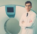 Doctor near computed tomography scanner young standing in a hospital Royalty Free Stock Images