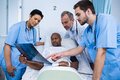 Doctor and nurse discussing x-ray with patient in ward Royalty Free Stock Photo