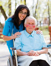 Doctor nurse with elderly patient beautiful in blue coat walking a kind lady in wheelchair in park Stock Image
