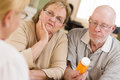 Doctor or nurse explaining prescription medicine to senior coupl attentive couple Stock Photo