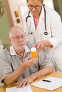Doctor or nurse explaining prescription medicine to senior man attentive Stock Images