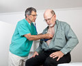 Doctor or Nurse Listens to Older Patient's Heart Stock Image