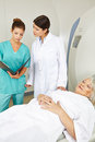 Doctor and nurse at mri looking medical records of senior patient Stock Photo