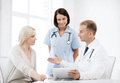 Doctor and nurse with patient in hospital healthcare medical technology showing something to on tablet pc Stock Image