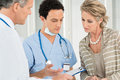 Doctor and nurse with patient in hospital medical record advising female Stock Photography