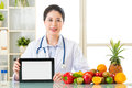 Doctor nutritionist with vegetable and fruit holding blank digit Royalty Free Stock Photo