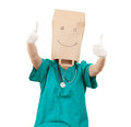 Doctor with paper bag on head keeping thumbs up Royalty Free Stock Image