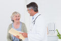 Doctor and patient conversing over reports Royalty Free Stock Photo