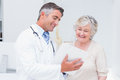 Doctor and patient discussing over reports happy in clinic Stock Images