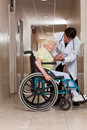 Doctor with patient on wheel chair at hospital Royalty Free Stock Photo